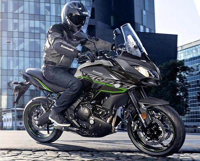 Le motard full équipé avec son pantalon de moto sur sa Kawasaki Versys